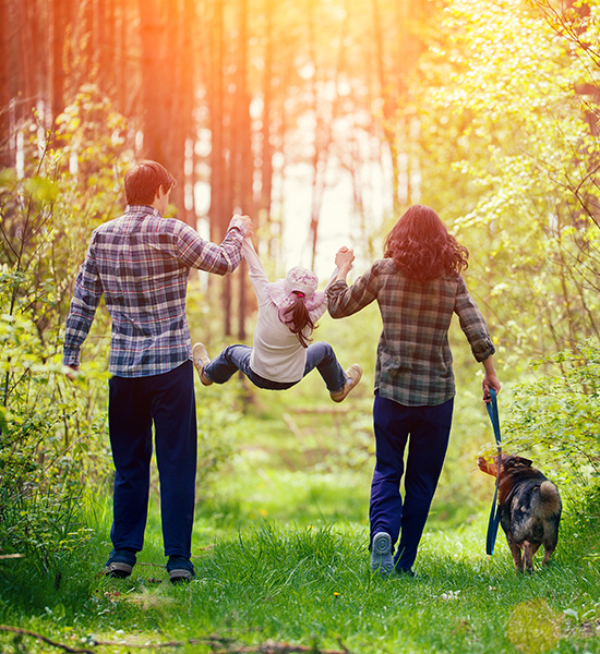 family walking in the woods with their daughter